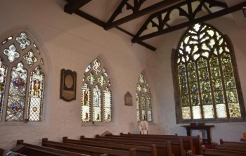 Figure 3: Image of interior of St. Denys church showing plaques and stained-glass windows on the walls by Frank Dwyer (York Press, 2018)