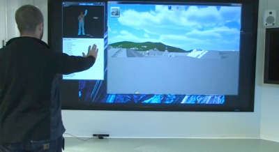 Figure 3: A presenter interacts with the MayaArch3D city using a Kinect-enabled interface; raising a hand towards the screen moves the user forward in virtual space (Image Copyright: Jennifer von Schwerin)